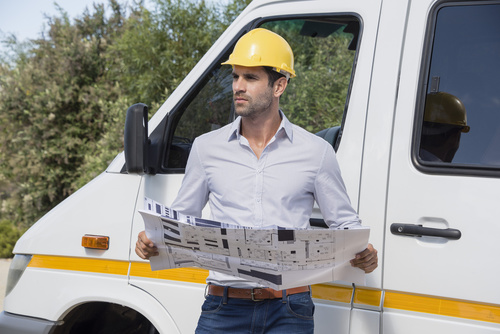 Male engineer reading a blueprint by van at site