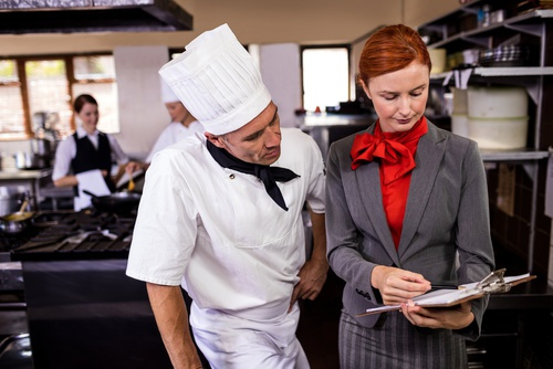 Female manager and male chef writing on clipboard in kitchen